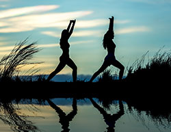 two women in a yoga pose standing outside